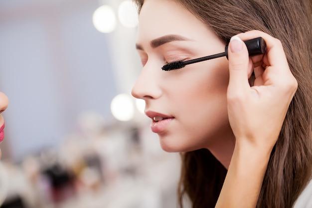 Feche a mão da mulher asiática, aplicar a sombra na pálpebra feminina. Foto Premium