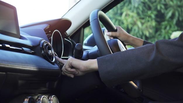 Feche a mão da mulher, ela apertar o botão iniciar no carro moderno. Foto Premium