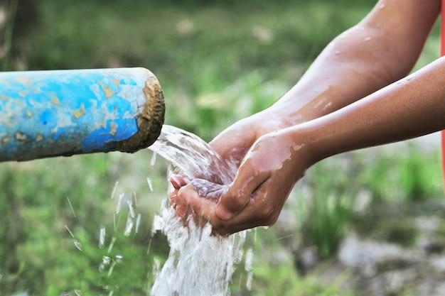 Feche a mão de crianças e respingo de gota de água no tubo Foto Premium