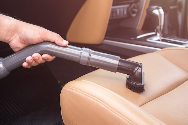 Feche a mão de pessoas segurando o aspirador de pó e limpeza dentro do carro suv Foto Premium