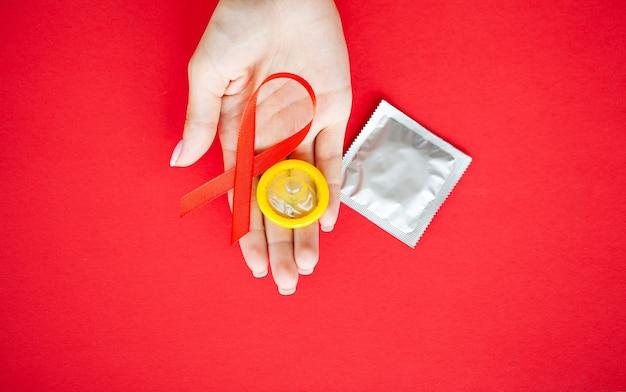 Feche a mão de uma mulher segurando a fita vermelha hiv, fita de conscientização do dia mundial da aids. Foto Premium