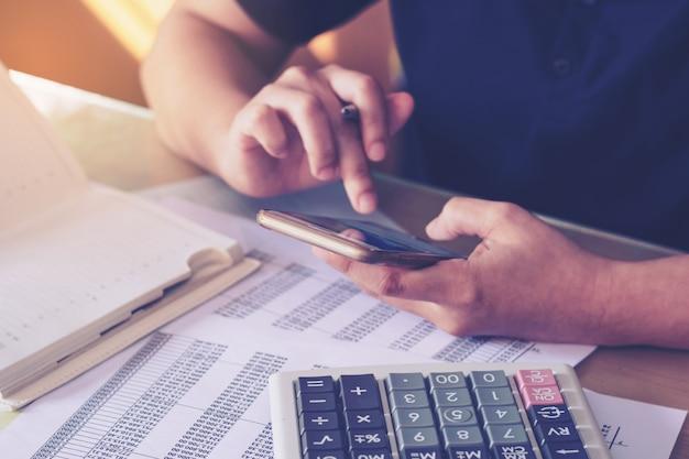 Feche a mão de uma mulher usando a calculadora e usando o smartphone na mesa de escritório. Foto Premium