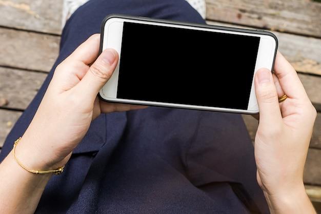 Feche a mão de uma mulher usando uma tecnologia de almofada de tela de toque Foto Premium