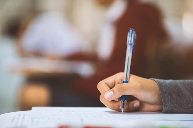 Feche a mão do aluno ler e escrever o exame com o estresse na sala de aula Foto Premium