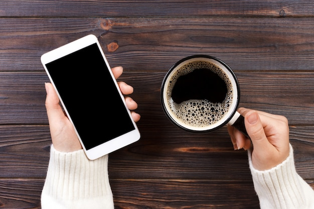 Feche a mão do homem de negócios mantém telefone inteligente com tela preta isolada sobre fundo de madeira e café Foto Premium