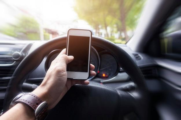 Feche a mão do homem usando o telefone inteligente enquanto ele está dirigindo o carro Foto Premium