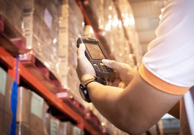 Feche a mão do trabalhador pressionando os botões do leitor de código de barras. equipamento informático para gestão de inventário em armazém. Foto Premium