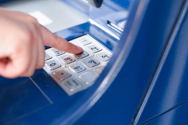 Feche a mão entrando pin ou senha em um caixa eletrônico Foto Premium