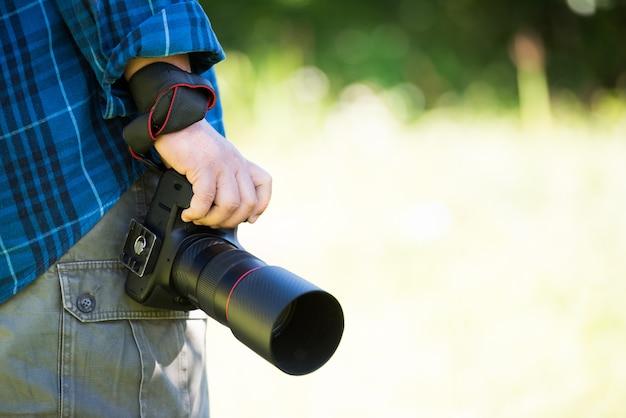 Feche a mão segurando a câmera dslr profissional Foto gratuita