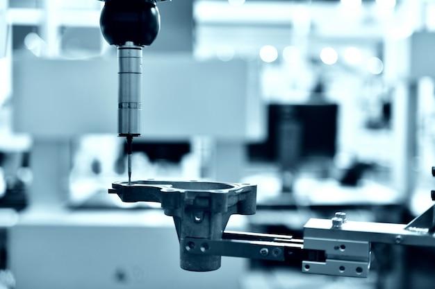 Feche a máquina de medição automática de coordenadas (cmm) para inspeção de peças de alta precisão durante o trabalho, tom azul Foto Premium