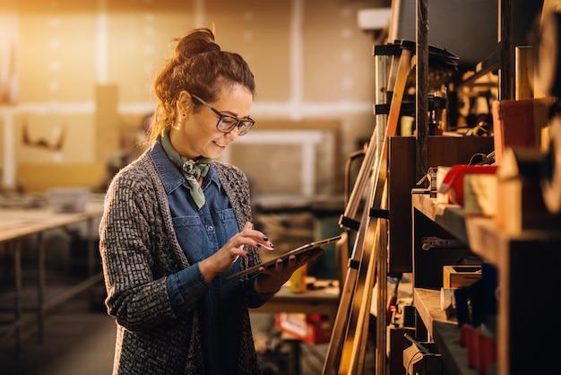 Feche a vista da mulher de negócios motivada profissional focada trabalhadora, segurando um tablet ao lado da prateleira com ferramentas na oficina de tecido. Foto Premium