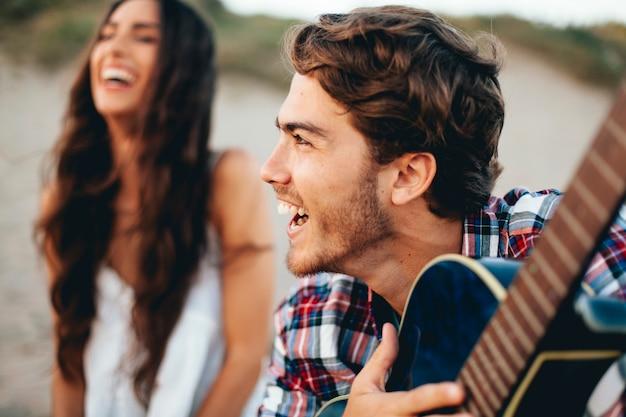 Feche a vista de amigos com guitarra Foto gratuita