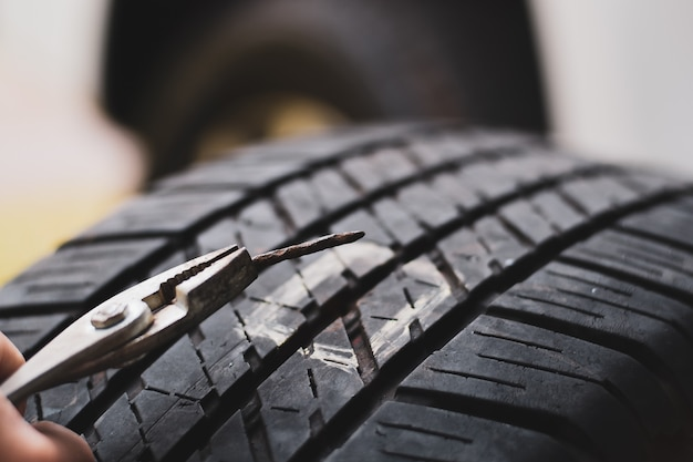 Feche acima da aderência no pneu, pneu furado o pneu está escapando da unha pode um pneu ser reparado Foto Premium