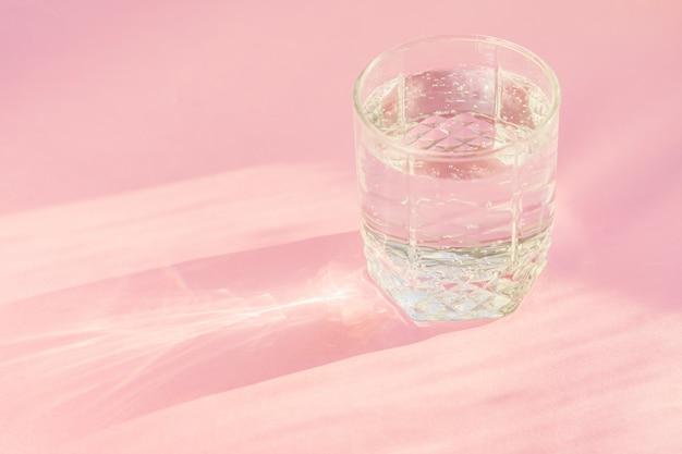 Feche acima da água gasosa no brilho transparente do vidro e do sol no fundo cor-de-rosa. Foto Premium