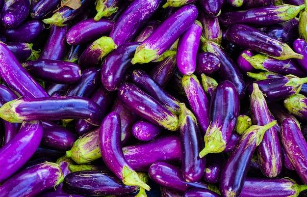 Feche acima da beringela ou da beringela roxas longas orgânicas no mercado Foto Premium