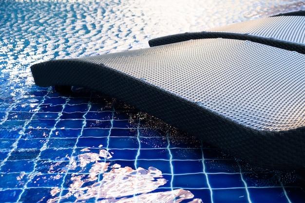 Feche acima da cadeira da associação do rattan ao lado da piscina com a reflexão azul da luz da água e do sol Foto Premium