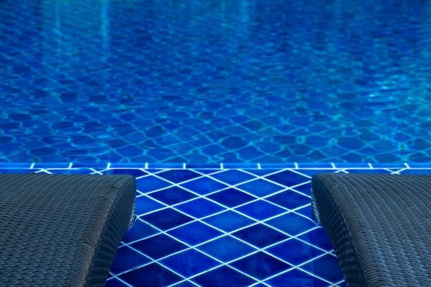 Feche acima da cadeira de piscina de vime ao lado da piscina com água azul Foto Premium