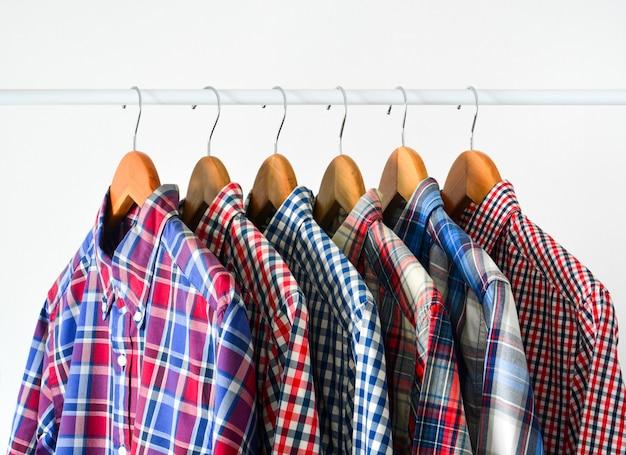 Feche acima da camisa quadriculada vermelha e azul de manga longa em cabide de madeira sobre branco Foto Premium