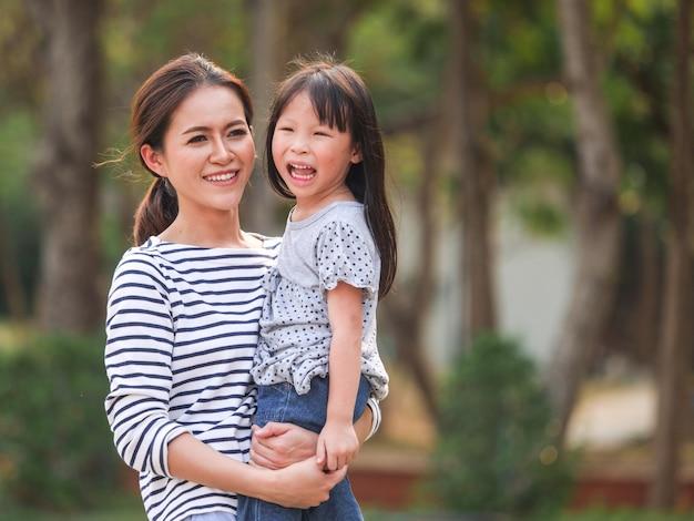 Feche acima da cara feliz da menina em seus braços da mãe. Foto Premium