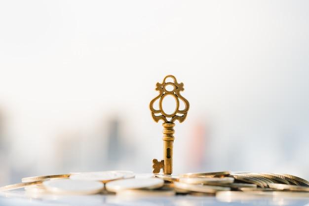 Feche acima da chave na pilha da moeda com arquitectura da cidade como fundos. Foto Premium