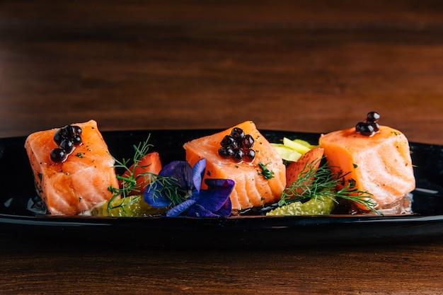 Feche acima da cobertura salmon grelhada média grelhada do cubo com caviar. Foto Premium
