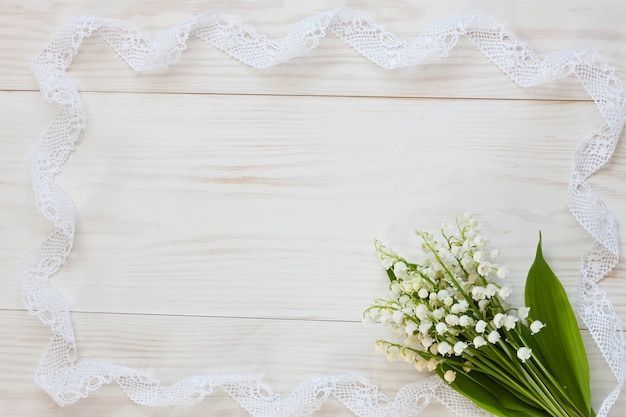 Feche acima da foto com o ramalhete dos lírios do vale no fundo de madeira branco Foto Premium