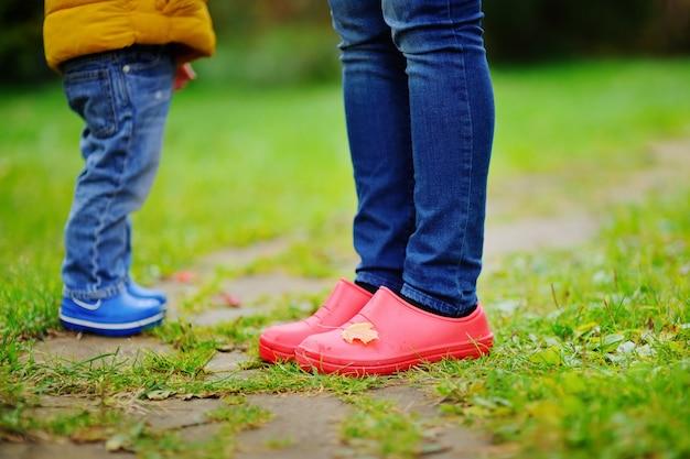 Feche acima da foto das pernas da criança e do adulto nas botas de borracha. família no outono. Foto Premium
