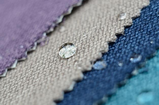 Feche acima da gota da água em amostras de matéria têxtil do gunny. conceito para superfícies limpas e impermeáveis Foto Premium