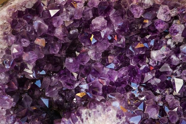 Feche acima da ideia de uma pedra de cristal de ametista violeta natural do geode. Foto Premium