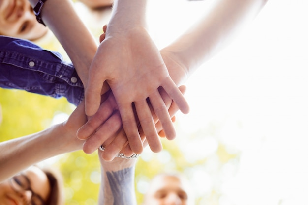Feche acima da imagem das mãos das pessoas juntas. símbolo do trabalho em equipe e unidade para alcançar um determinado objetivo Foto Premium