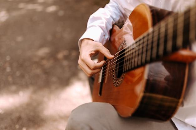 Feche acima da imagem do homem que joga a guitarra acústica ao ar livre. Foto Premium