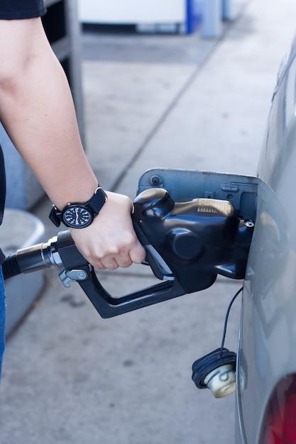 Feche acima da mão da mulher colocando o gás no carro no posto de gasolina Foto gratuita