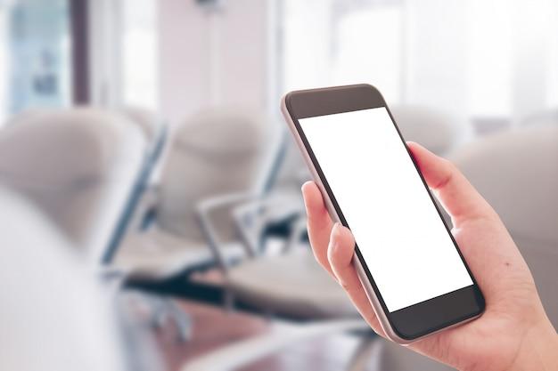 Feche acima da mão da mulher usando um telefone esperto com a tela vazia no aeroporto. Foto Premium