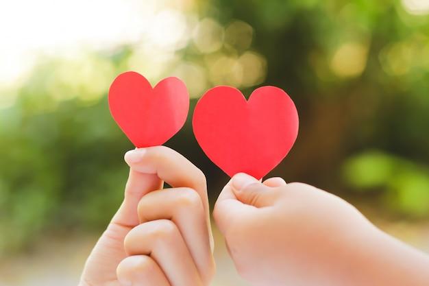 Feche acima da mão das crianças que guardam o mini coração no fundo verde. Foto Premium