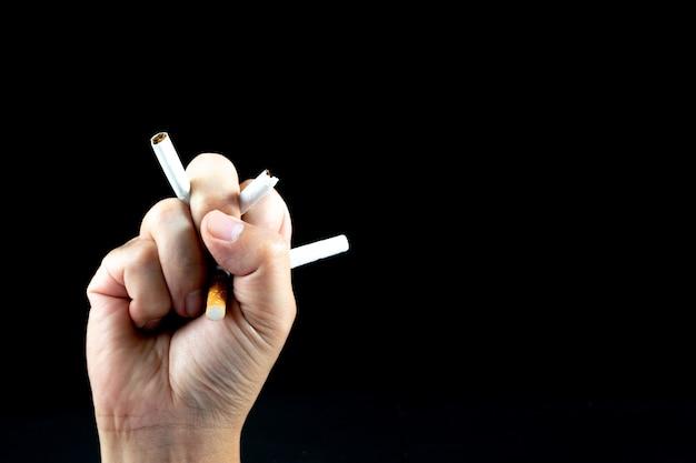 Feche acima da mão do homem que esmaga e que destrói cigarros no fundo preto. Foto Premium