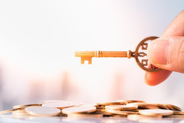 Feche acima da mão do homem que guarda chave na pilha da moeda com arquitectura da cidade como fundos. Foto Premium