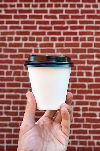 Feche acima da mão masculina que guarda a xícara de café do livro branco, contra uma parede de tijolo vermelho. aproveitando o café para ir Foto Premium