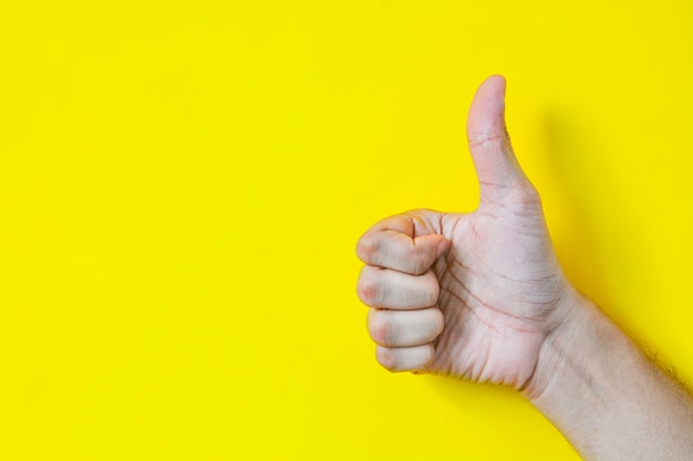Feche acima da mão masculina que mostra os polegares acima do sinal sobre o amarelo Foto Premium