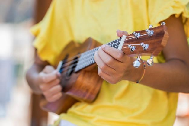Feche acima da menina com ukulele Foto Premium