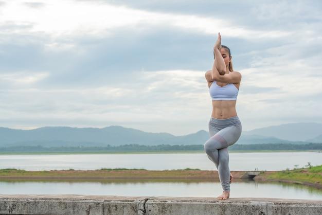 Feche acima da mulher asiática que faz o pose da ioga na praia. Foto Premium