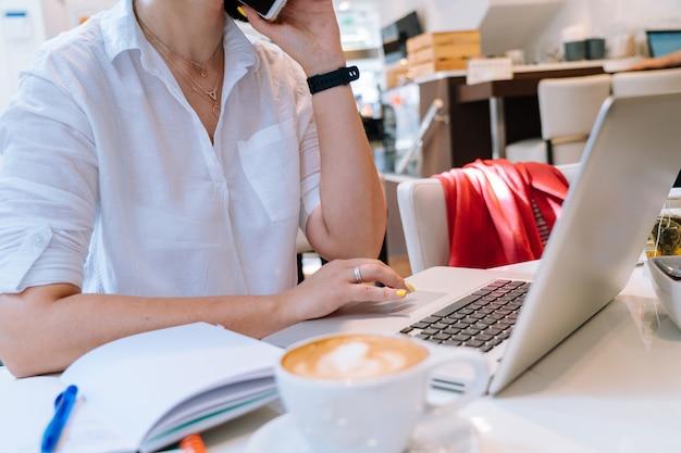 Feche acima da mulher de negócio das mãos que senta-se no escritório coworking e que datilografa em seu computador do teclado do portátil. Foto Premium