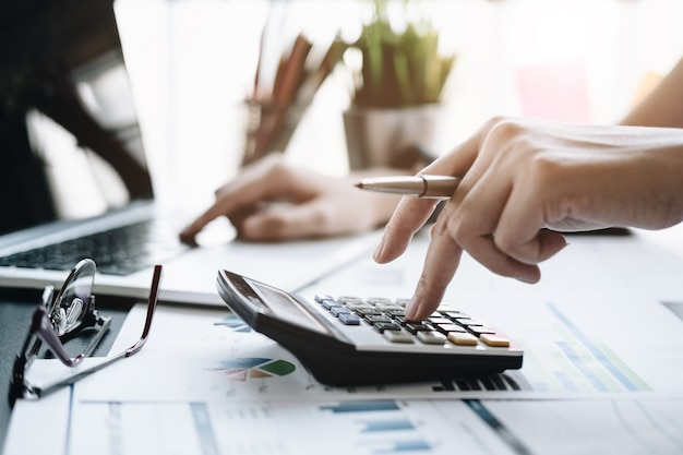 Feche acima da mulher de negócio que usa a calculadora e o portátil para fazer a finança da matemática Foto Premium
