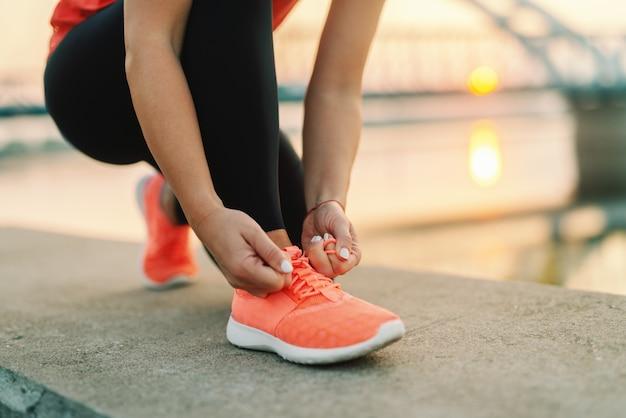 Feche acima da mulher desportiva que amarra o laço ao ajoelhar-se ao ar livre, na ponte do fundo. conceito de fitness ao ar livre. Foto Premium