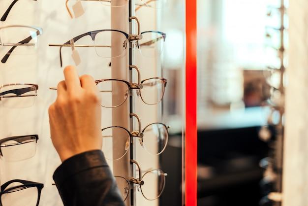 Feche acima da mulher que toma vidros da prateleira. Foto Premium