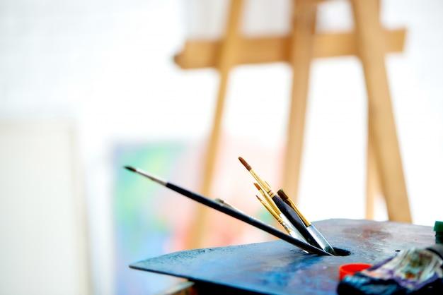 Feche acima da paleta com a escova no estúdio brilhante da arte. Foto Premium