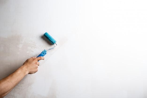 Feche acima da parede da pintura da mão com rolo. Foto gratuita