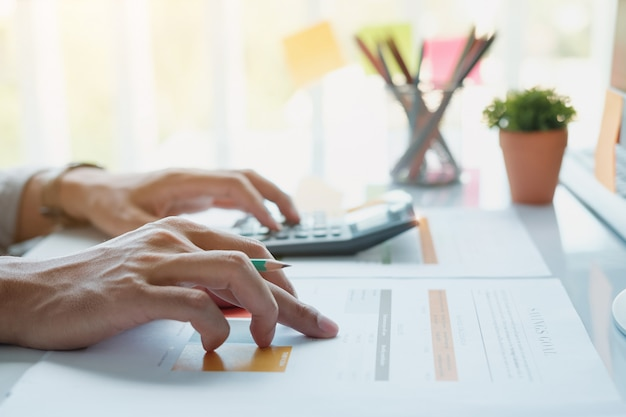 Feche acima da pena de terra arrendada do homem de negócios ou do contabilista que trabalha na calculadora para calcular dados de negócio Foto Premium