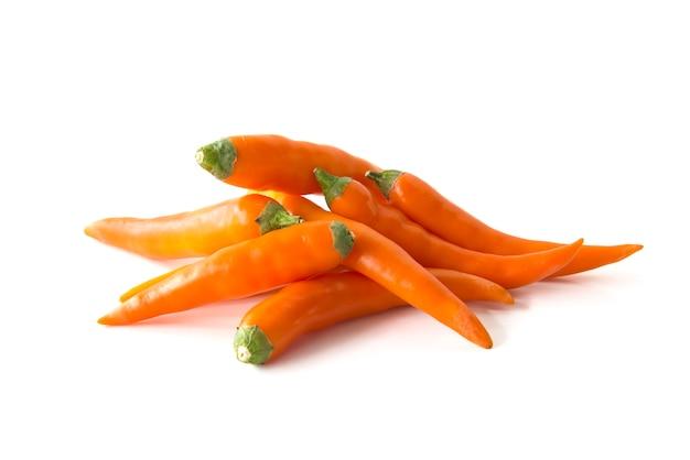 Feche acima da pimenta de pimentão quente alaranjada isolada em um fundo branco Foto Premium