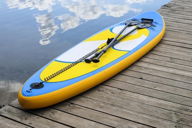Feche acima da placa inflável do sup perto do rio. placa sup, placa de remo de pé Foto Premium