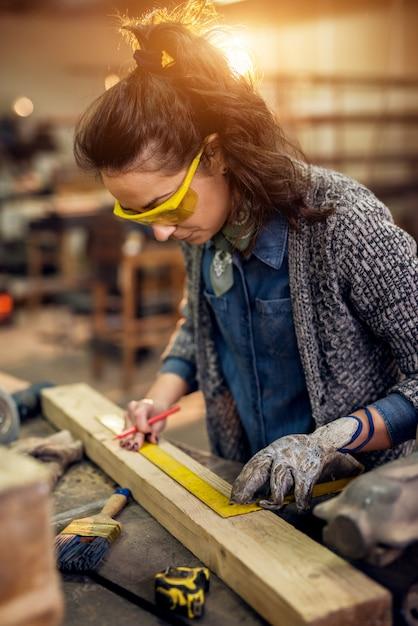 Feche acima da vista da mulher séria profissional carpinteiro profissional focada segurando a régua e lápis ao fazer marcas na madeira à mesa na oficina de tecidos. Foto Premium